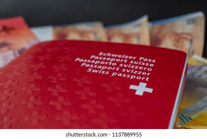 swiss passport and money close up on black background switzerland citizenship and currency