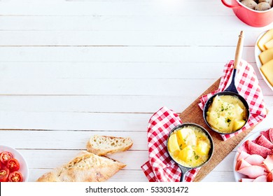 Swiss raclette cheese corner border with copy space with tomatoes, bread, cold meats and two skillets with boiled potatoes toped with melted cheese on rustic red and white cloths