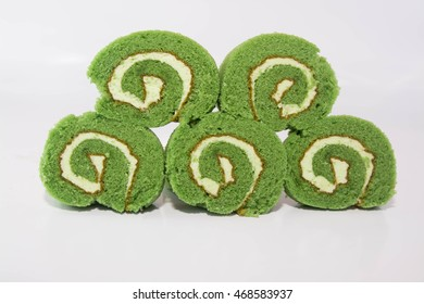 Swiss roll cake with matcha green tea on white background.