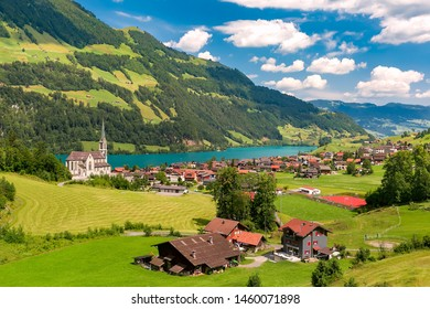 Swiss village Lungern with its traditional houses and Neo-Gothic church along the lake Lungerersee, canton of Obwalden, Switzerland