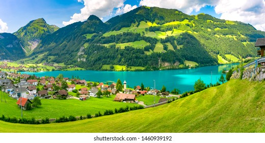 Swiss village Lungern with its traditional houses and old church tower Alter Kirchturm along lovely emerald green lake Lungerersee, canton of Obwalden, Switzerland