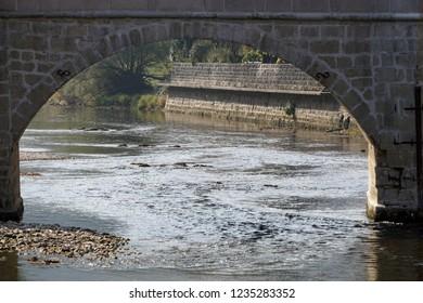 In the Swiss village of Saint-Ursanne, the Doubs river flowing through the main stone bridge