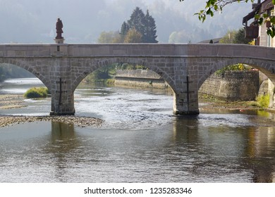 In the Swiss village of Saint-Ursanne, the main bridge on the Doubs river with the statue of a saint