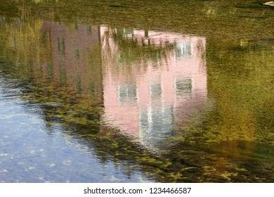 In the Swiss village of Saint-Ursanne, a pink house reflected in the Doubs river (fuzzy image due to the reflection)