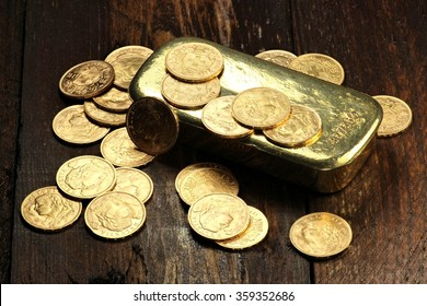 swiss vreneli gold coins and a gold ingot on wooden background
