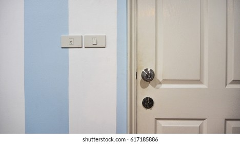 Switch and door on blue stripe wallpaper
