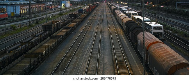 switch yard with trains, wagons, cargo at sunset