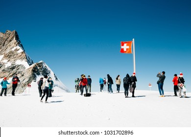 Switzerland - August 20, 2016 : Swiss flag and tourist people on Jungfrau snowy mountain summit