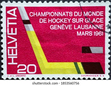 Switzerland - Circa 1961 : a postage stamp printed in the swiss showing a yellow ice hockey stick and puck. Text.: European and World Hockey Championships in Geneva