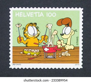 SWITZERLAND - CIRCA 2014: postage stamp printed in Switzerland showing an image of the cartoon characters the cat Garfield and the dog Odie, circa 2014.