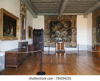 GRUYÈRES, SWITZERLAND / EUROPE on JULY 2017: Historical interior with wooden ceiling and floor, paintings and tapestries on wall at medieval castle in swiss town in warm sunny day.