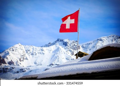 Switzerland flag Over Swiss Mountains in a Winter Day.