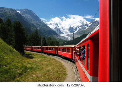 Switzerland, July 2012: The Bernina Express train of the Rhaetian Railway, with the Morteratsch glacier in the background, Switzerland.