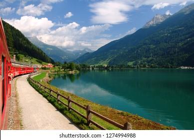 Switzerland, July 2012: Swiss Mountain Train Bernina Express at Lake of Poschiavo