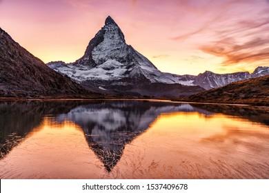 Switzerland, Matterhorn. Epic sunset view of Matterhorn mountain peak reflected in Riffelsee lake. Seasonal autumnal scenery. Picturesque Swiss landscape.