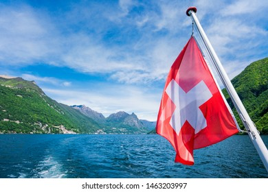 Switzerland national flag in a sunny day on a stunning lake Lugano background view