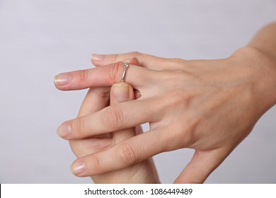 Swollen Hands. Woman traing to remove stuck ring off a swollen finger