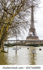 The swollen Seine during the winter flooding episode of January 2018, with half immersed road signs and street lights in the foreground and the Eiffel tower and Bir-Hakeim bridge in the background.
