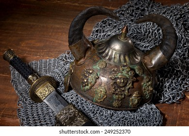sword, chain armor and the soldier's helmet with horns on a wooden background with beautiful light