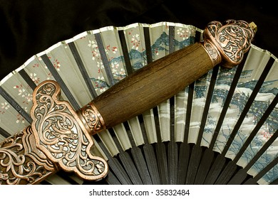 a Sword handle laid across a fan