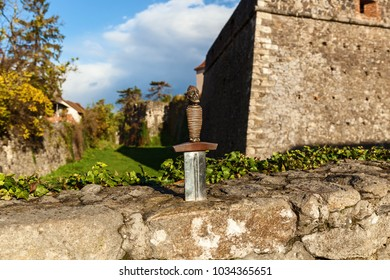 Sword in stone. Sword of King Arthur in stone. Steel blade weapon of Camelot with a handle in the form of a knight.Sword in the stone near the castle.Old castle walls and weapon.