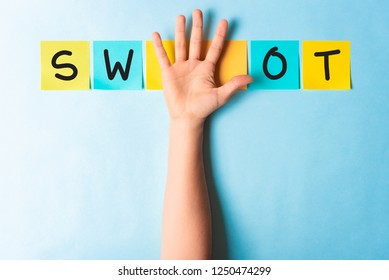 SWOT analysis banner concept. Hand upward with open palm and multicolored paper notes on blue background.