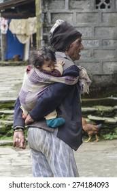 SYANGJA BAZAR, NEPAL - SEPT 20: a man carrying his grandson, Sept 20, 2014 in Syangja Bazar, Nepal.