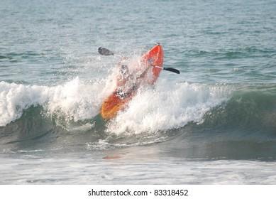 Syaulita Mexico ocean kayaker breaking through the crest of the a small ocean wave.