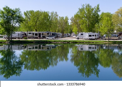 SYCAMORE, ILLINOIS - MAY 16 2018: Recreational vehicles parked at the waters edge with a peaceful reflection on the tranquil pond early spring with campers enjoying the peace and stillness.