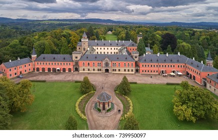 Sychrov Chateau, Sichrow, aerial, central view on unique example of Neo-Gothic castle, surrounded by english park in romantic style. Romantic castle in Czech landscape, under dramatic sky. Czechia.
