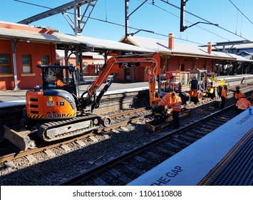 Sydney, AU - MAY 20, 2018: Railway construction workspace. The orange heavy cranes with engineers and workers are checking the train railroad at Lidcombe station.