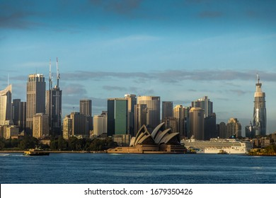 Sydney, Australia - 10th February 2020: A German photographer visiting Sydney in Australia, taking pictures of the skyline seen from a park during a cloudy but warm day in summer.