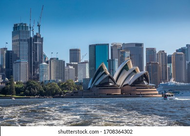Sydney, Australia - 10th February 2020: A German photographer visiting Sydney in Australia, taking pictures of the skyline seen from a park during a cloudy but warm day in summer. Seen from a ferry.