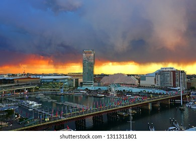 SYDNEY, AUSTRALIA -13 JUL 2018- Fiery orange sunset view under a cloudy sky of the Sofitel hotel tower and Darling Harbour, a busy modern neighborhood in Sydney, New South Wales.