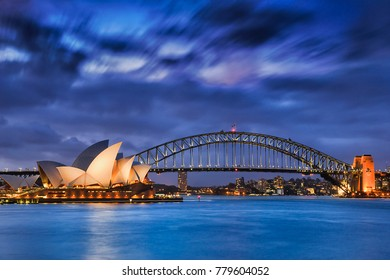 Sydney, Australia, 18 March 2017: World famous Sydney Opera House and Harbour bridge at sunset. Blurred clouds and lights of landmarks reflect in blurred waters of Harbour.