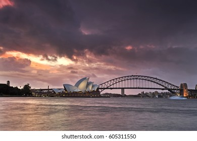 Sydney, Australia - 19 March 2017: Sydney opera house and Harbour bridge during stormy weather and orange sunset around Sydney Harbour.