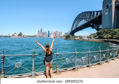 Sydney, Australia - 20 February 2016: young female tourist exploring Sydney Harbour in summer with view of opera house, skyline and the bridge