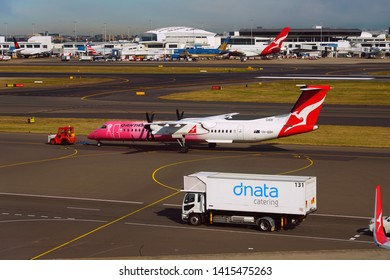 SYDNEY, AUSTRALIA -20 JUL 2018- View of a De Havilland Dash 8 airplane from Australian airline Qantas (QF) painted in Breast Cancer pink ribbon livery colors at the Kingsford Smith airport (SYD).