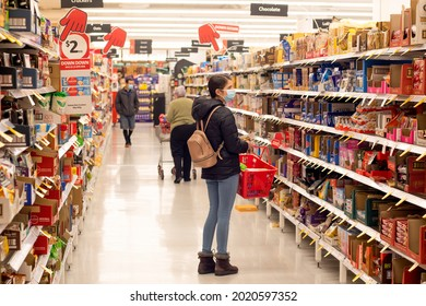 Sydney, Australia 2021-07-21 Teenage girl man wearing mask surveying grocery aisle at Coles supermarket during COVID-19 Delta outbreak lockdown.