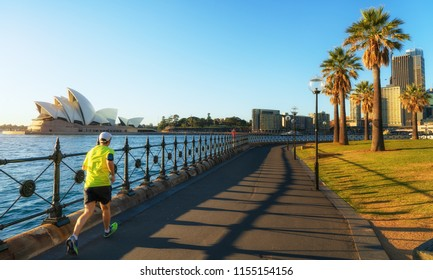 Sydney, Australia - 30th of July 2018. Women exercising & running past Sydneys iconic Circular Quay, Landmark Opera House with Harbour Bridge in the background in the morning on a warm summer day.