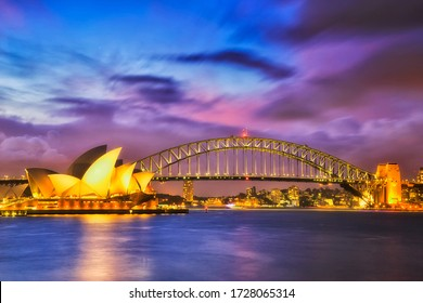 Sydney, Australia - 5 January 2020: Waterfront of Sydney city CBD on shores of Sydney Harbour around the harbour bridge at sunset with blurred water and clouds.