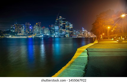 Sydney, Australia - Apr 21, 2019: Night view of the iconic Millers Point and Barangaroo suburbs (right), from the park beside Balmain East Wharf ferry terminal. Features colorful lighting.