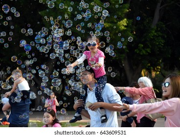 Sydney, Australia - Apr 23, 2017. Kids catching and having fun and with soap bubbles in Hyde Park (Sydney, NSW, Australia).
