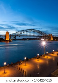 Sydney, Australia - April 21, 2019: People at Circular Quay viewing Sydney Harbour Bridge at dusk.