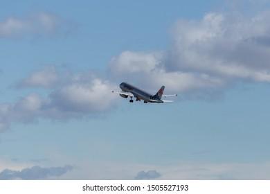 Sydney, Australia - August 10, 2019: Jetstar Airbus A320 flying into a cloudy sky.