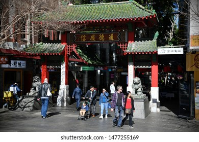 Sydney, Australia - August 12, 2019: People pass through the Chinatown gate in the city centre.