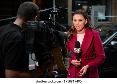 Sydney, Australia - August 13, 2019: A news reporter broadcasts live on TV at a crime scene as police investigate a suspected murder in the city's CBD.