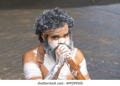 SYDNEY, AUSTRALIA - AUGUST 26, 2016: Unidentified body painted aborigine street musician playing on his traditional didgeridoo at Circular quay in Sydney, Australia.