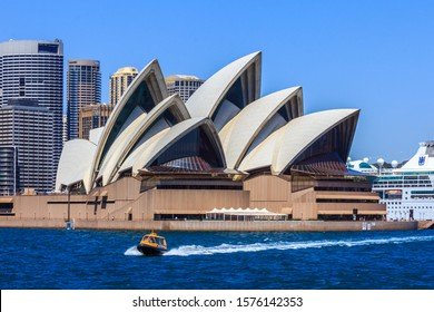 Sydney, Australia - December 19th 2013: A water taxi speeds past the Opera House in Sydney Harbour. The building is world famous.