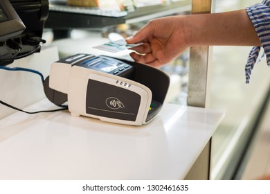 Sydney, Australia - December 2018: young woman uses pay wave eftpos over the counter in a store